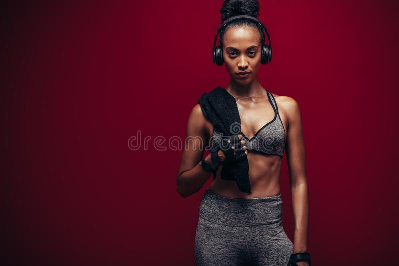 African female athlete resting after her workout. Woman with perfect body standing over red background. African female athlete resting after her workout stock photo