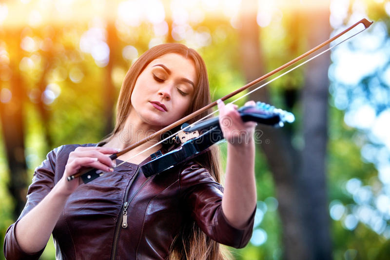 Woman perform music on violin park outdoor. Girl performing jazz . Woman perform music on violin in park outdoor. Girl performing jazz on city street . Spring royalty free stock images