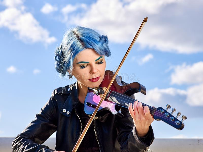 Woman perform music on violin park outdoor. Girl performing jazz. royalty free stock images