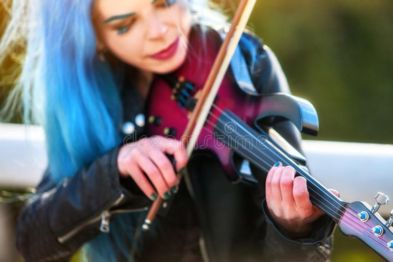 Woman perform music on violin park outdoor. Girl performing jazz. royalty free stock photography