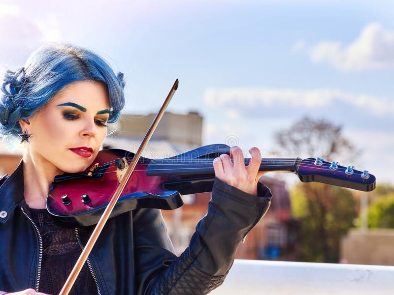 Woman perform music on violin park outdoor. Girl performing jazz. royalty free stock photos
