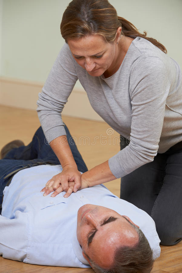 Woman Performing CPR On Man Collapsed On Floor. Woman Performs CPR On Man Collapsed On Floor stock image