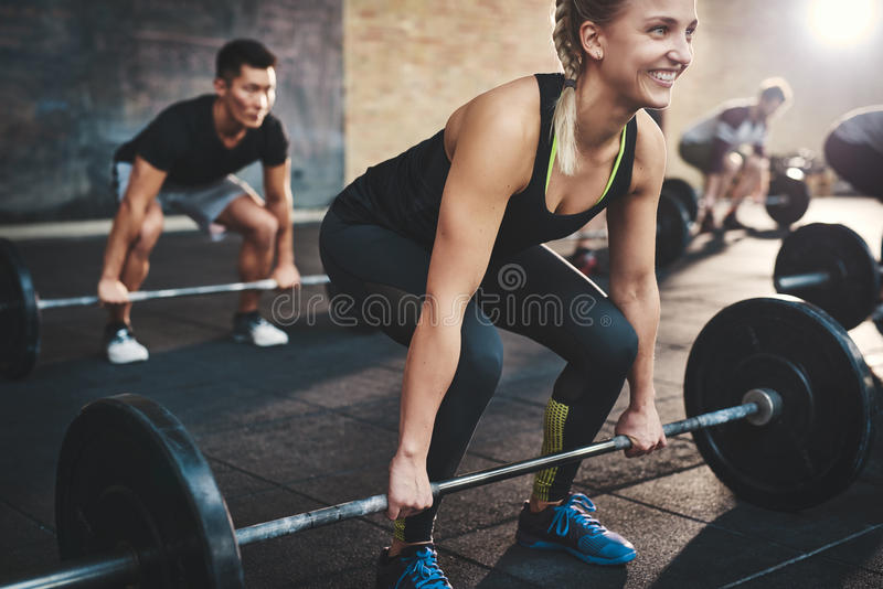 Woman performing dead lift barbell exercise royalty free stock image