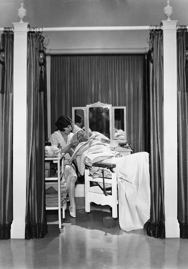 Woman performing facial. (All persons depicted are no longer living and no estate exists. Supplier grants that there will be no model release issues stock image