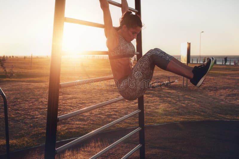 Woman performing hanging leg raises. royalty free stock images