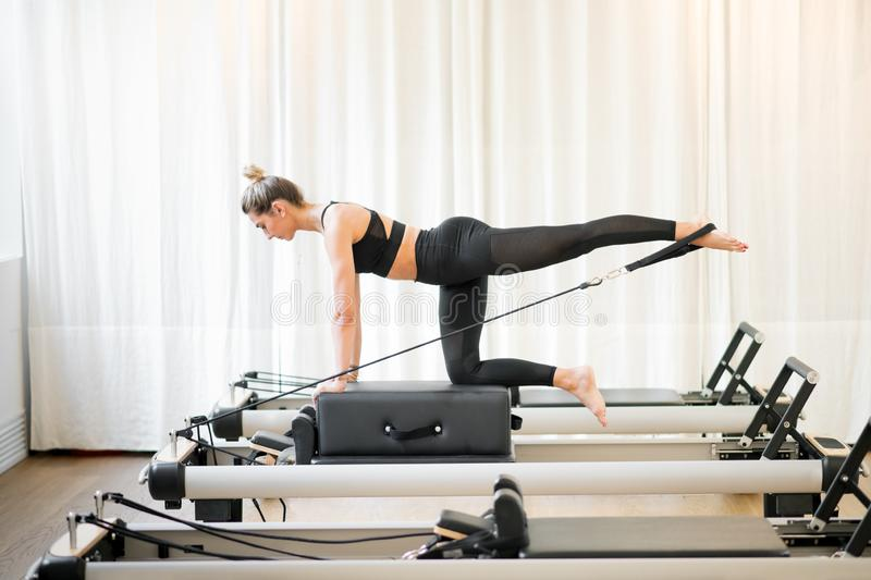 Woman performing a pilates diagonal stabilisation royalty free stock photo