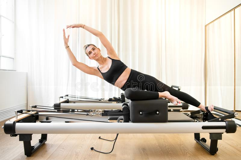 Woman performing a pilates yoga mermaid exercise stock images
