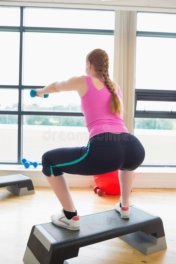Woman performing step aerobics exercise with dumbbells. Rear view of a woman performing step aerobics exercise with dumbbells in a gym royalty free stock photo