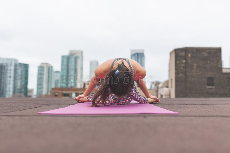Woman performing yoga on building roof royalty free stock images