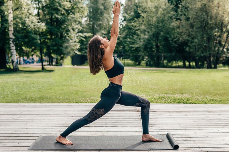 Woman performing yoga on exercise mat royalty free stock photos