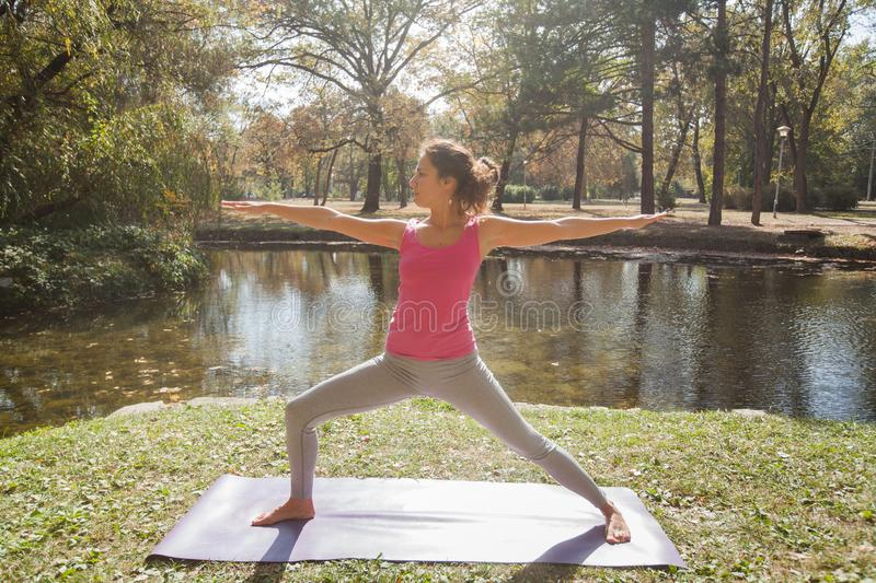 Woman Performing Yoga Exercise In Warrior Pose At The City Park stock photography