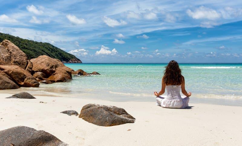 Woman performing yoga on a tropical beach stock photos