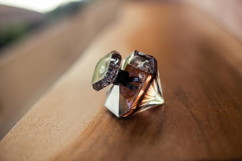 Woman perfume bottle, diamond shape. Woman perfume bottle with the shape of a diamond on a brown wooden table, background blurred stock photos
