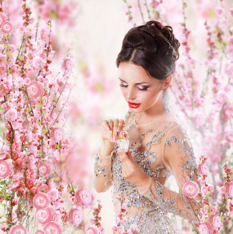 Woman with Perfume over Floral Background stock photos