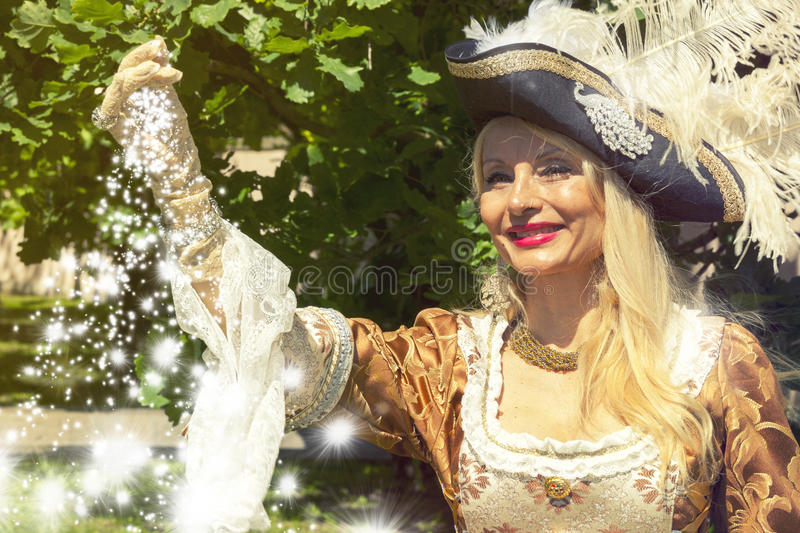 Woman in period costume with shower of stars from the hand. royalty free stock images