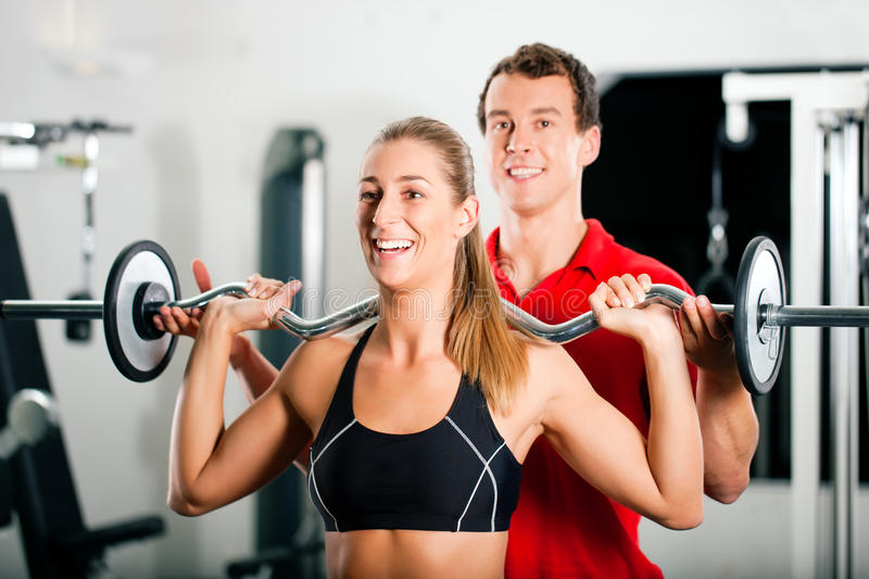 Woman with Personal Trainer in gym. Woman in gym with personal fitness trainer exercising power gymnastics with a barbell royalty free stock photos