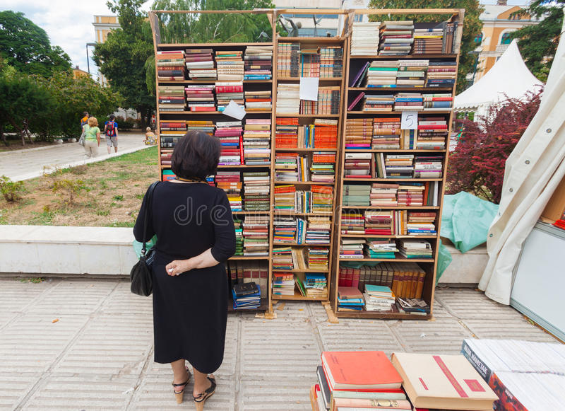 Woman perusing bookshelves on street market. SARAJEVO, BOSNIA AND HERZEGOVINA - AUGUST 11: Woman perusing bookshelves on street market on August 11, 2012 in stock image