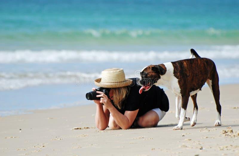 Woman & pet dog on tropical beach taking photos