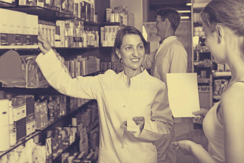 Woman pharmacist in drug store stock image
