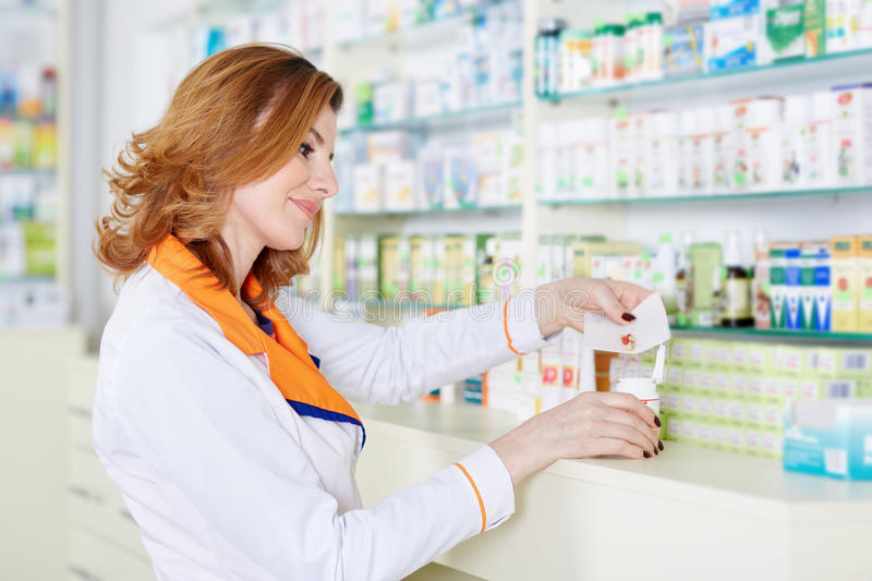 Woman pharmacist over blurred background royalty free stock images