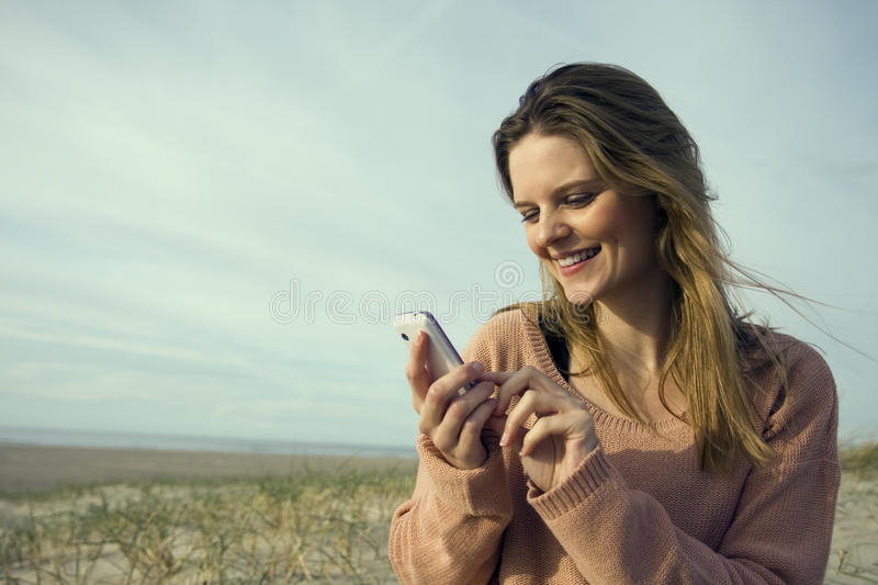 Woman with mobile on beach. Happy young woman using mobile telephone on beach with cloudscape background stock photo
