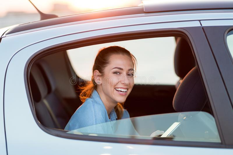 Woman with phone on the back seat of a car stock photography