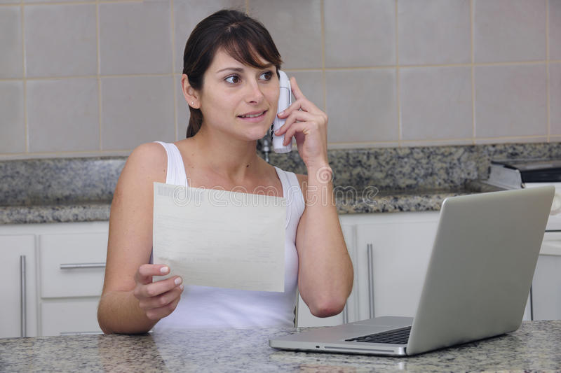 Woman on phone with bill. Woman holding a bill, shopping online, talking on the phone royalty free stock images