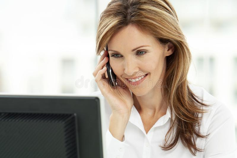 Woman on the phone - businesswoman using phone in office - corporate executive. Portrait of a woman on the phone - businesswoman using smartphone in office royalty free stock photo