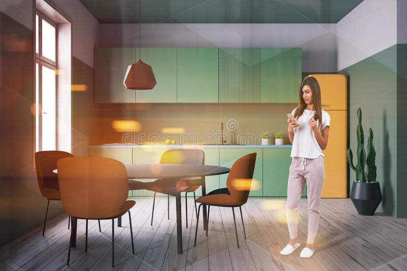 Woman with phone in green kitchen royalty free stock photo