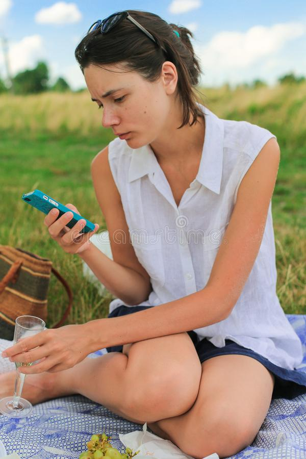 Woman with phone having rest. Serious concentrated young woman drinking wine, sitting on blanket in park, using her phone stock image
