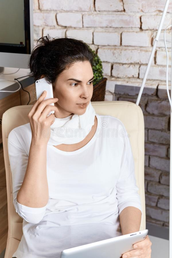 Woman on phone holding tablet. Attractive adult woman working using modern technology talking on phone holding tablet royalty free stock photography