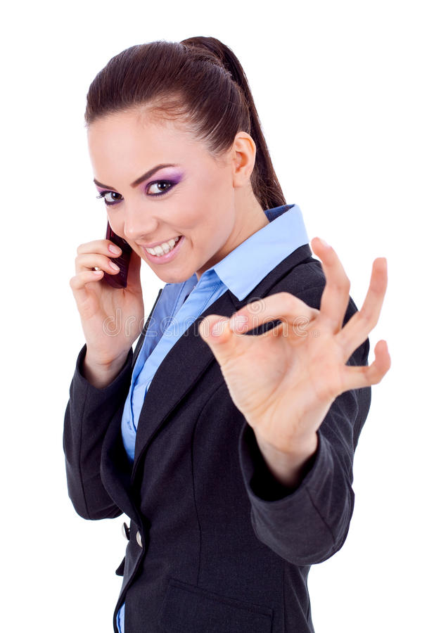 Woman with phone and ok gesture. Happy business woman with phone and ok gesture, isolated royalty free stock images