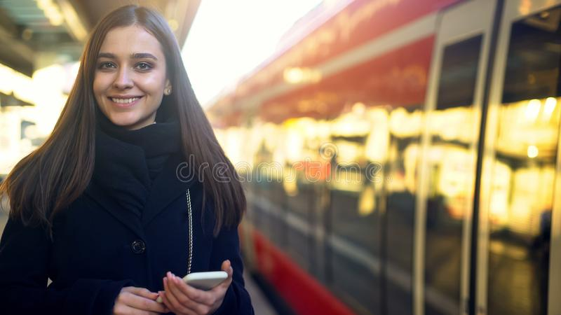 Woman with phone smiling near train, quick mobile payment for tickets technology royalty free stock photography