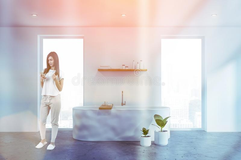 Woman with phone in white bathroom. Young woman with smartphone standing in white bathroom interior with comfortable bathtub standing between windows. Toned royalty free stock photo