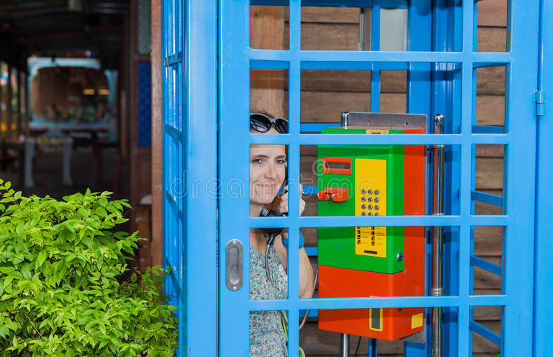 Woman phoned in a colorful phone booth. stock photo