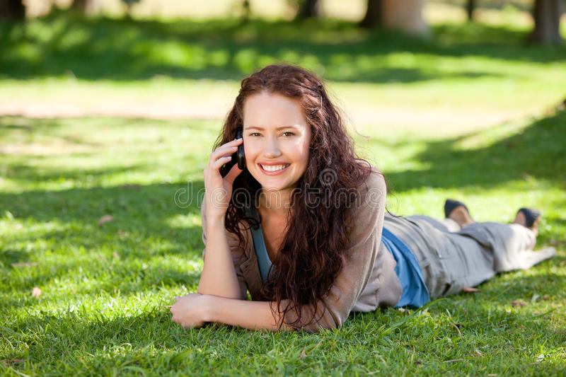 Woman phoning in the park stock photo
