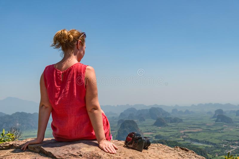 Woman phortographer relaxing on mountain top royalty free stock photo