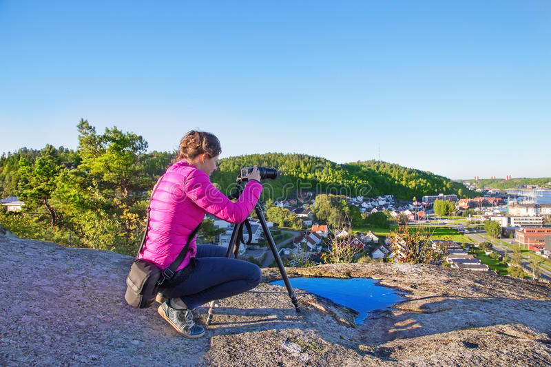 Woman with a photocamera early in the morning on a mount in Sand stock image