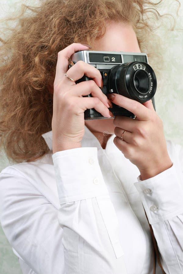 Woman photographer. Holding photo-camera royalty free stock photography