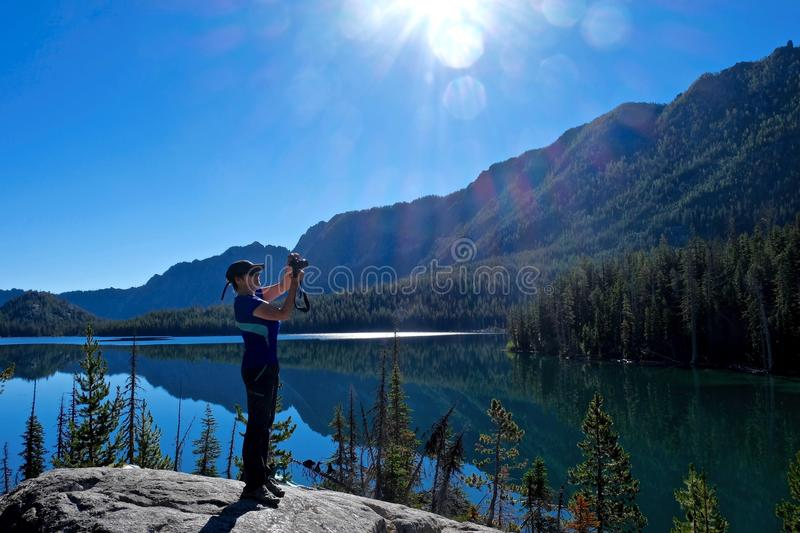 Woman photographer by alpine lake with reflection in calm water. stock photos