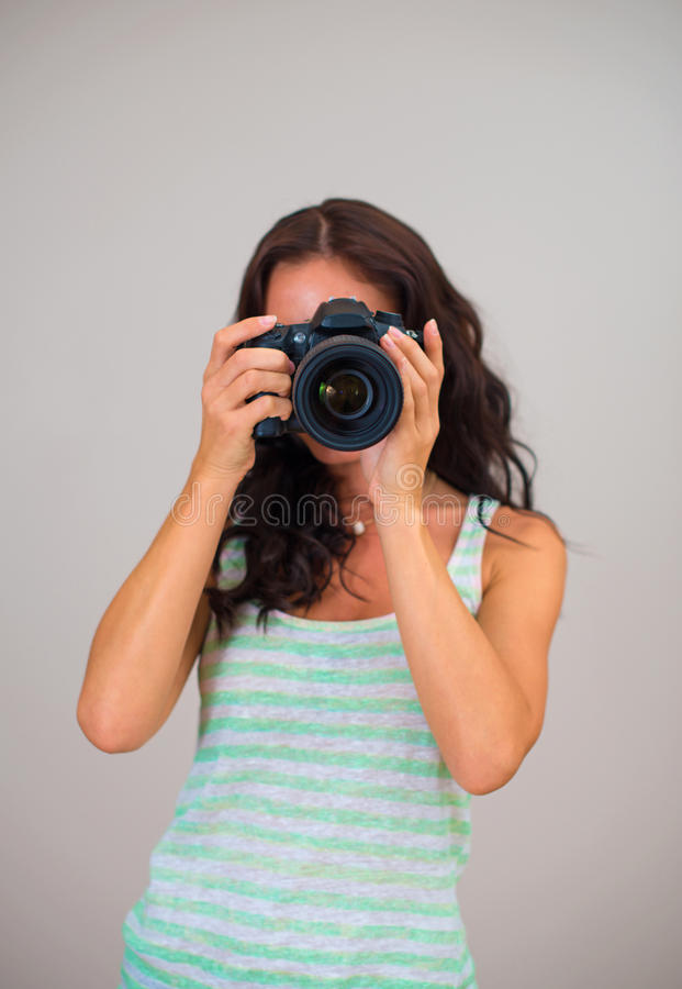 Woman-photographer. Attractive brunette woman-photographer takes pictures stock photos