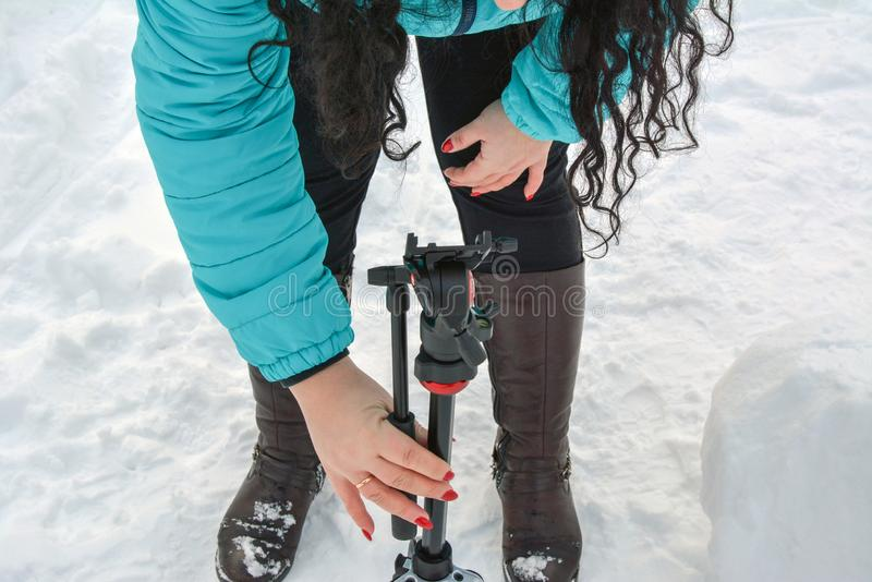 Woman photographer lays out a Monfroto tripod on the snow.  Russia, Tatarstan, March 03, 2019 stock photo