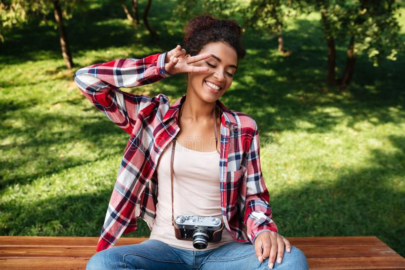 Woman photographer sitting outdoors in park. stock photo