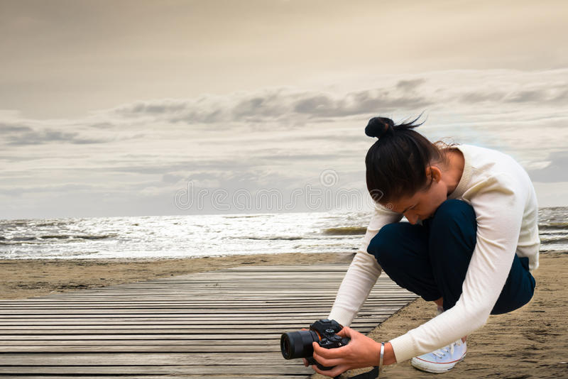 Woman photographer sitting on the sand at sunset with a camera in his hands stock image
