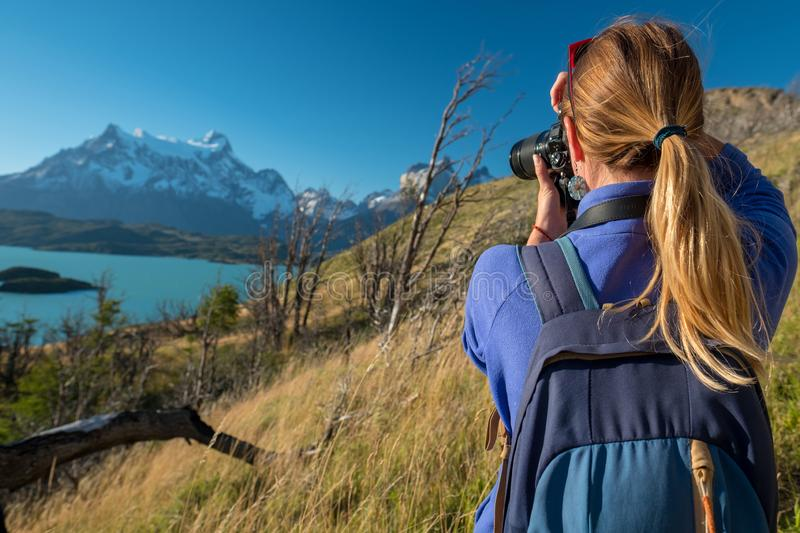 Woman photographer. Takes photo of the mountains in Torres del Paine National Park in Chile royalty free stock images