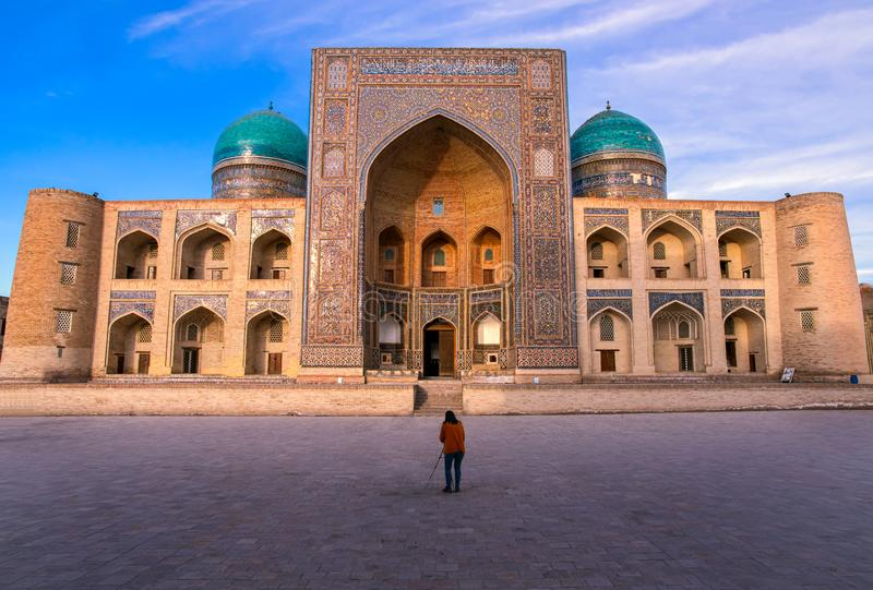 A woman-photographer takes a photograph of one of the main attractions of Bukhara Uzbekistan stock photography