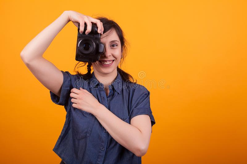 Woman photographer is taking images with dslr camera in studio over yellow background royalty free stock image