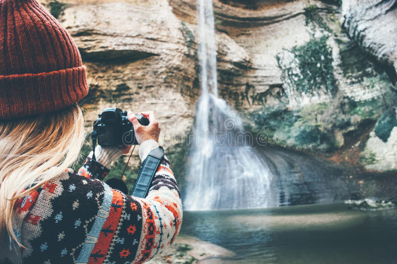 Woman photographer taking photo of waterfall royalty free stock photography