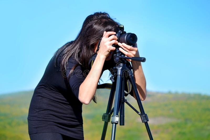 Woman Photographer Taking Photos with Digital Camera and Tripod stock photography