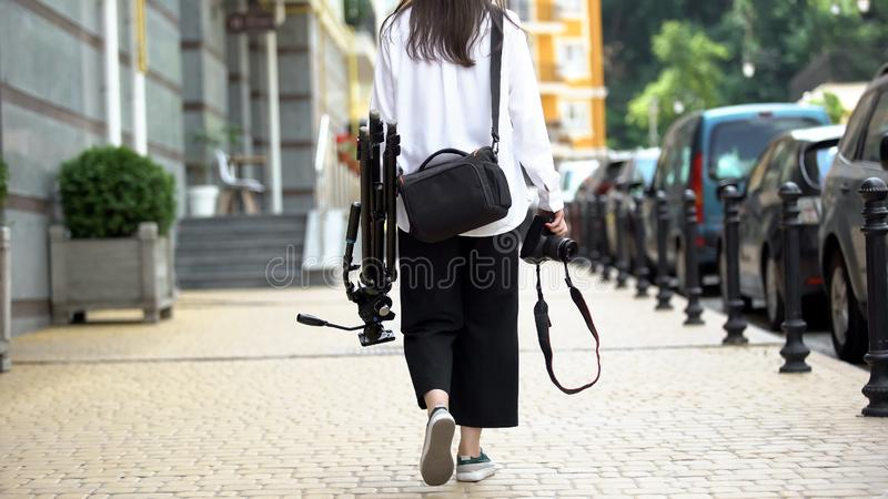 Woman photographer walking on street with equipment, going to work, photoshoot stock photos